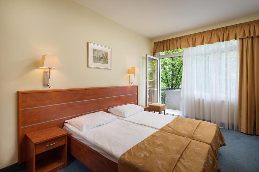 A bed or beds in a room at Benczur Hotel