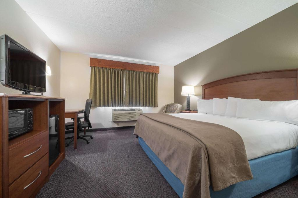 A bed or beds in a room at AmericInn by Wyndham Hutchinson