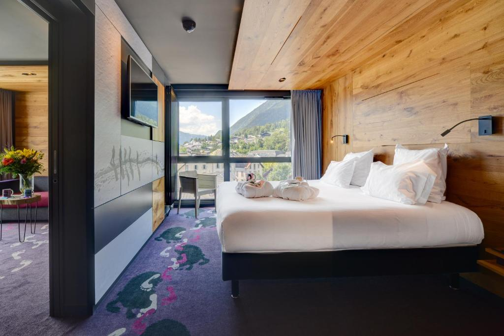 A bed or beds in a room at Alpina Eclectic Hotel