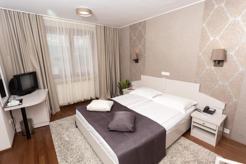 Un pat sau paturi într-o cameră la Hunguest Hotel Fenyõ
