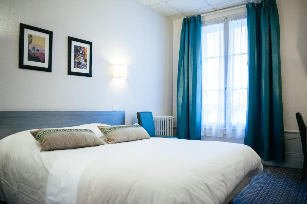 A bed or beds in a room at Citotel Le Carmin