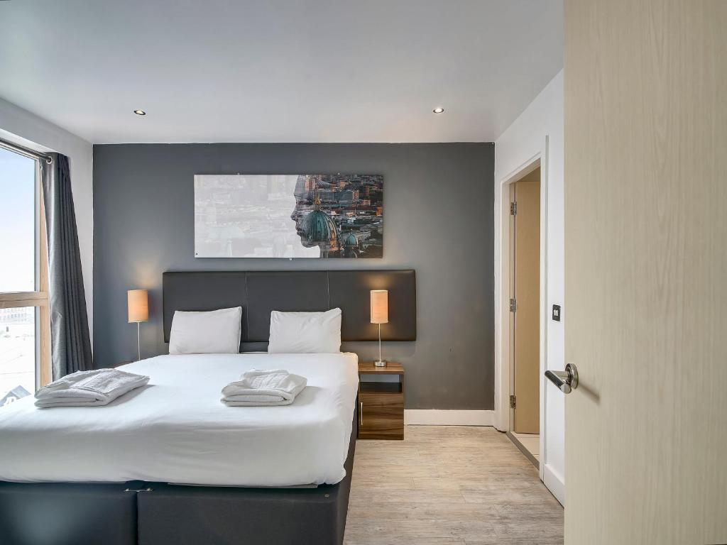 A bed or beds in a room at Living by BridgeStreet, Manchester City Centre