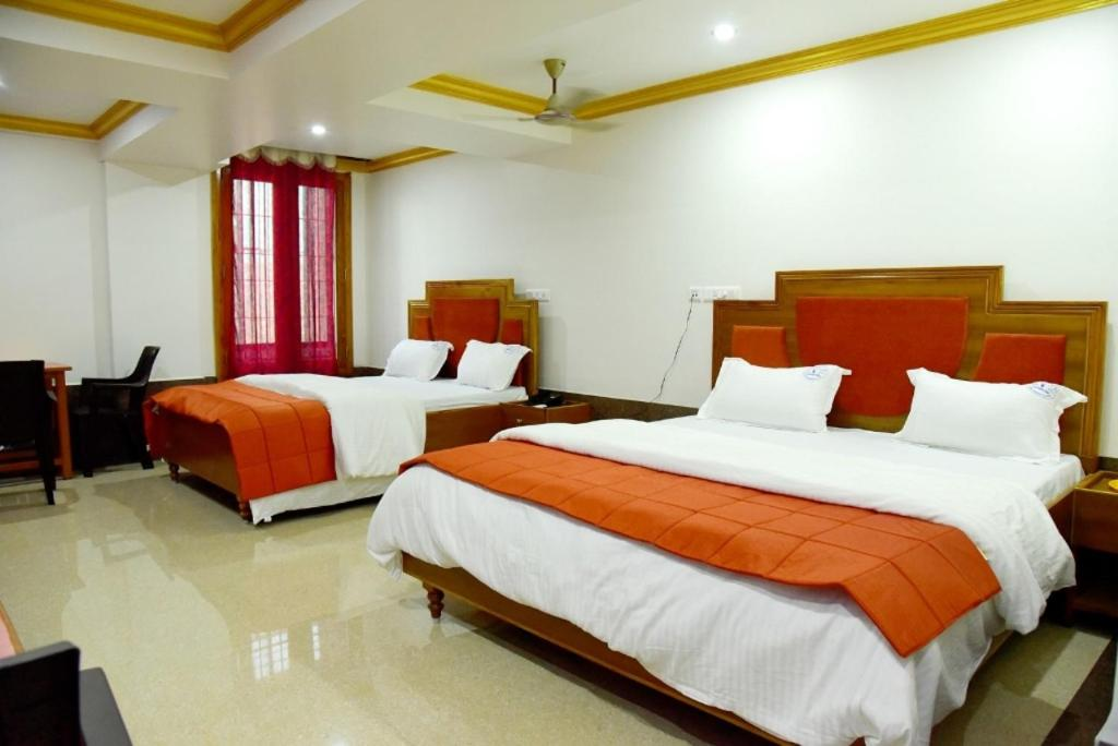 A bed or beds in a room at Hotel Chembiyan