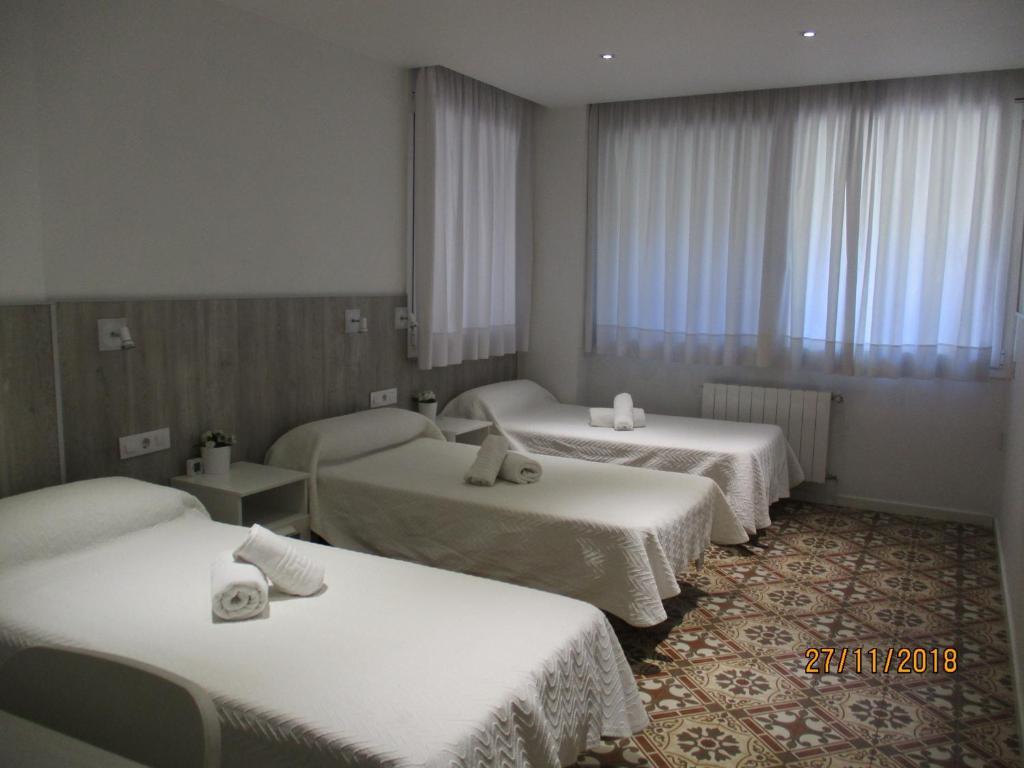 A bed or beds in a room at Hostal Nova Barcelona