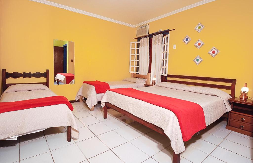 A bed or beds in a room at Pousada Talismã