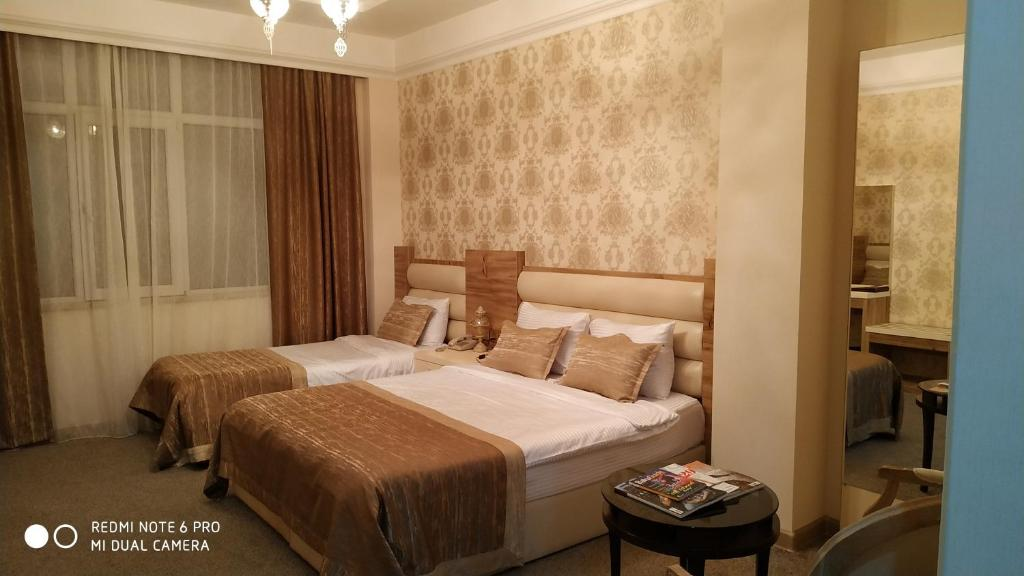 A bed or beds in a room at Bosfor Hotel Baku