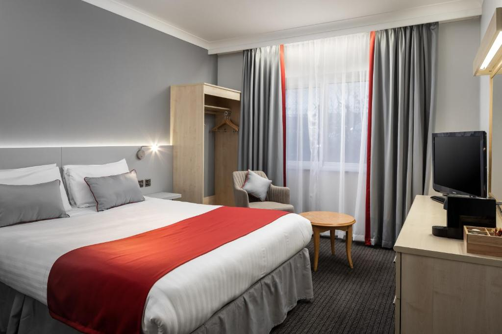 A bed or beds in a room at Ramada London Finchley