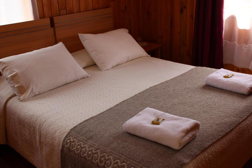 A bed or beds in a room at Hostal Don Luis Puyuhuapi