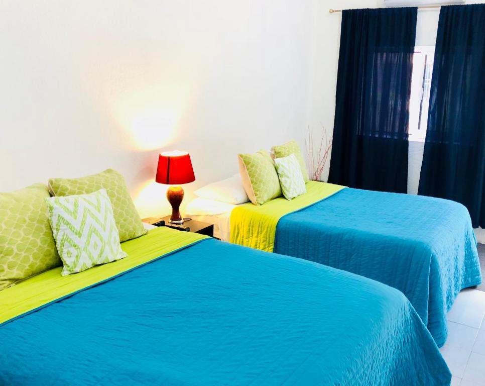 A bed or beds in a room at Villa Las Flores Cozumel- Downtown