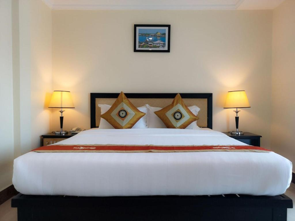 A bed or beds in a room at Cardamom Hotel & Apartment