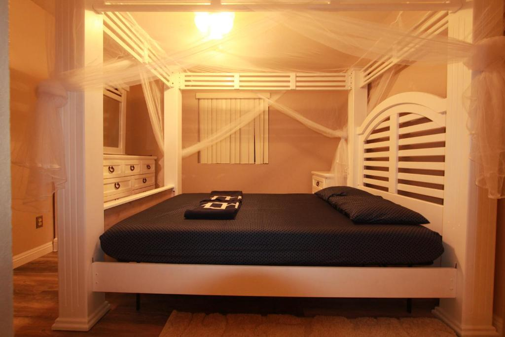 A bed or beds in a room at Queen's White Canopy Bed w/ Free WiFi Parking 4 miles to Red Rock