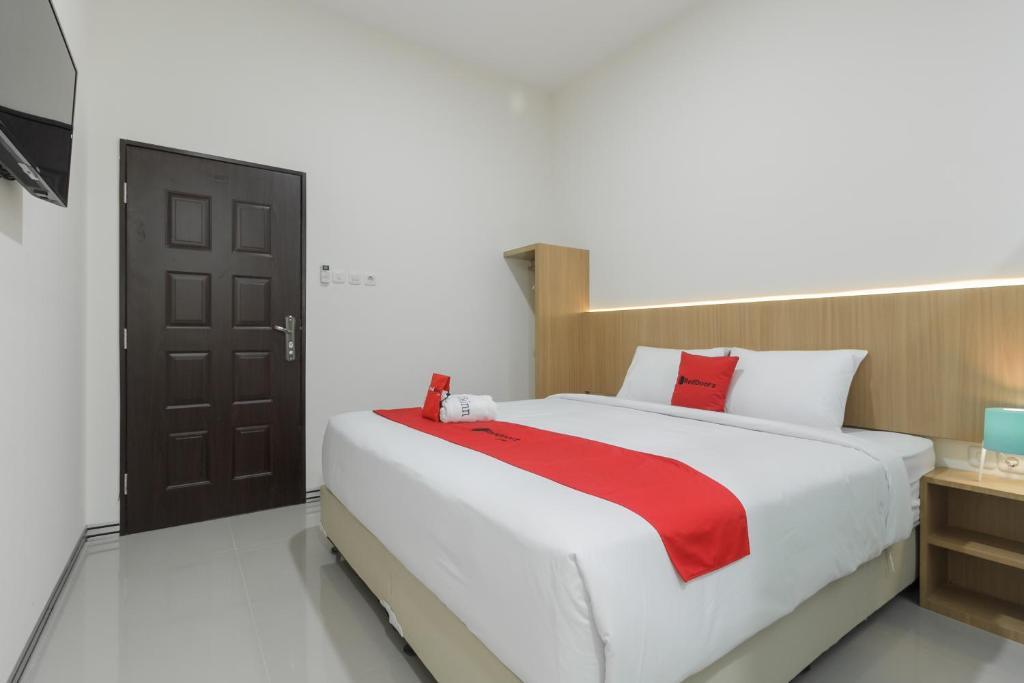 A bed or beds in a room at RedDoorz near Mall SKA Pekanbaru