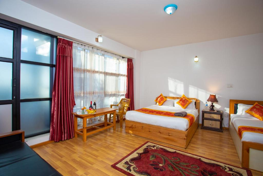 A bed or beds in a room at The Boudha Inn