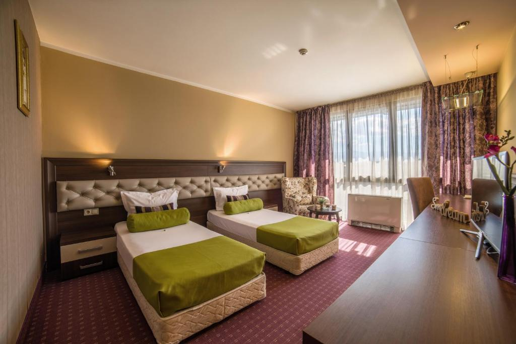 A bed or beds in a room at Business Hotel Plovdiv