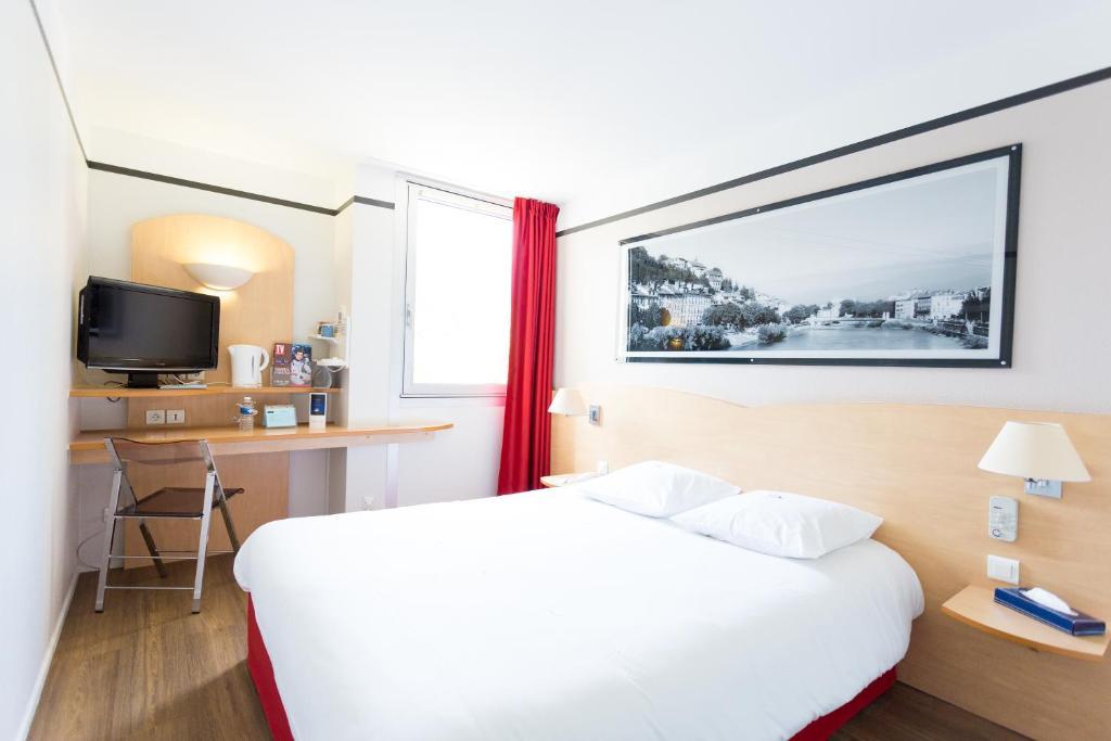 Un ou plusieurs lits dans un hébergement de l'établissement Kyriad Grenoble Eybens Parc des Expositions