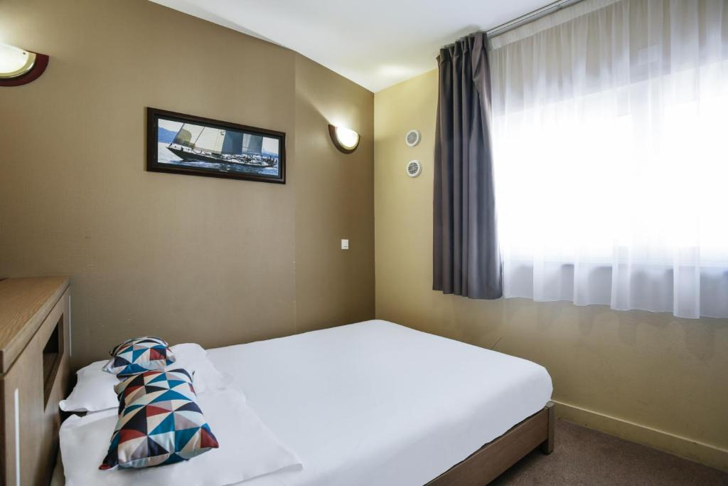 A bed or beds in a room at Appart'City Nice Acropolis