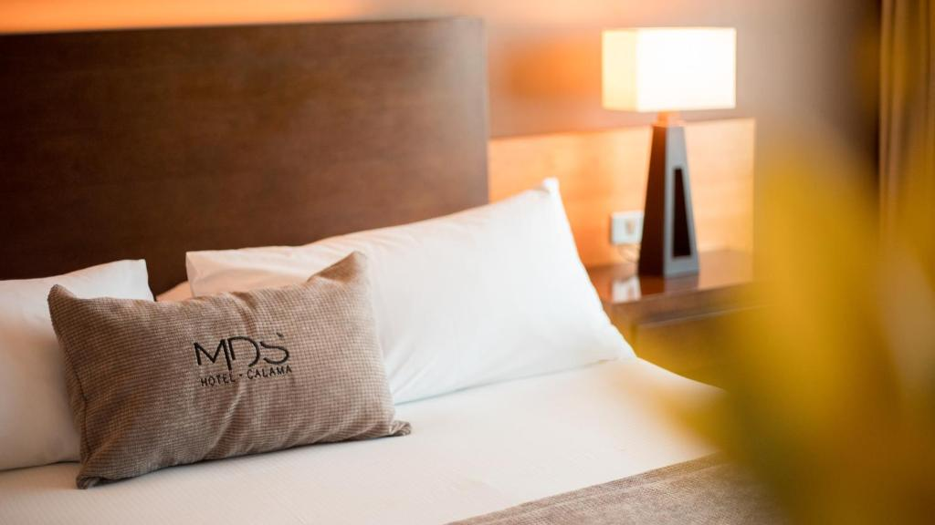 A bed or beds in a room at MDS Hotel Calama