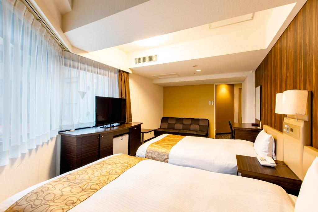 A bed or beds in a room at Hotel Wing International Shinjuku