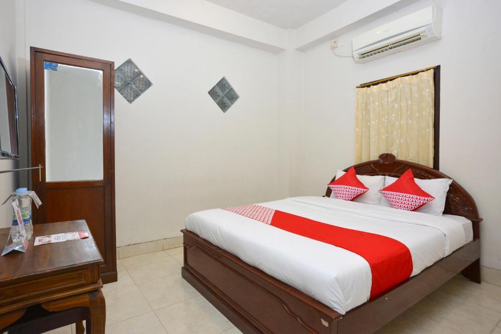 Tempat tidur dalam kamar di OYO 586 Hotel Wijaya