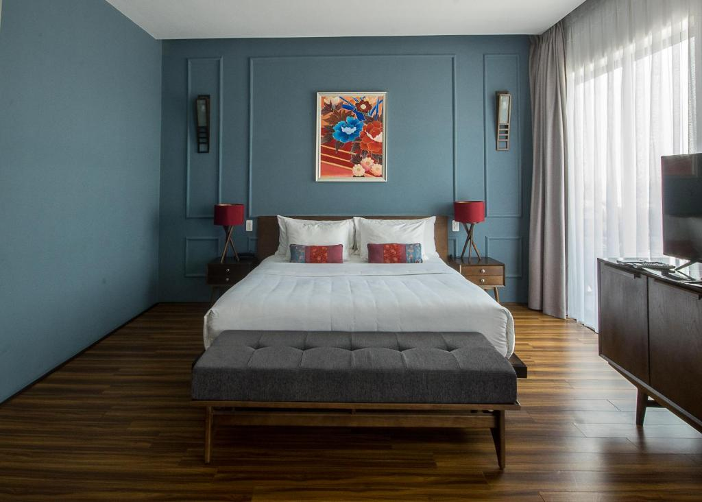 A bed or beds in a room at Danang Boutique Hotel