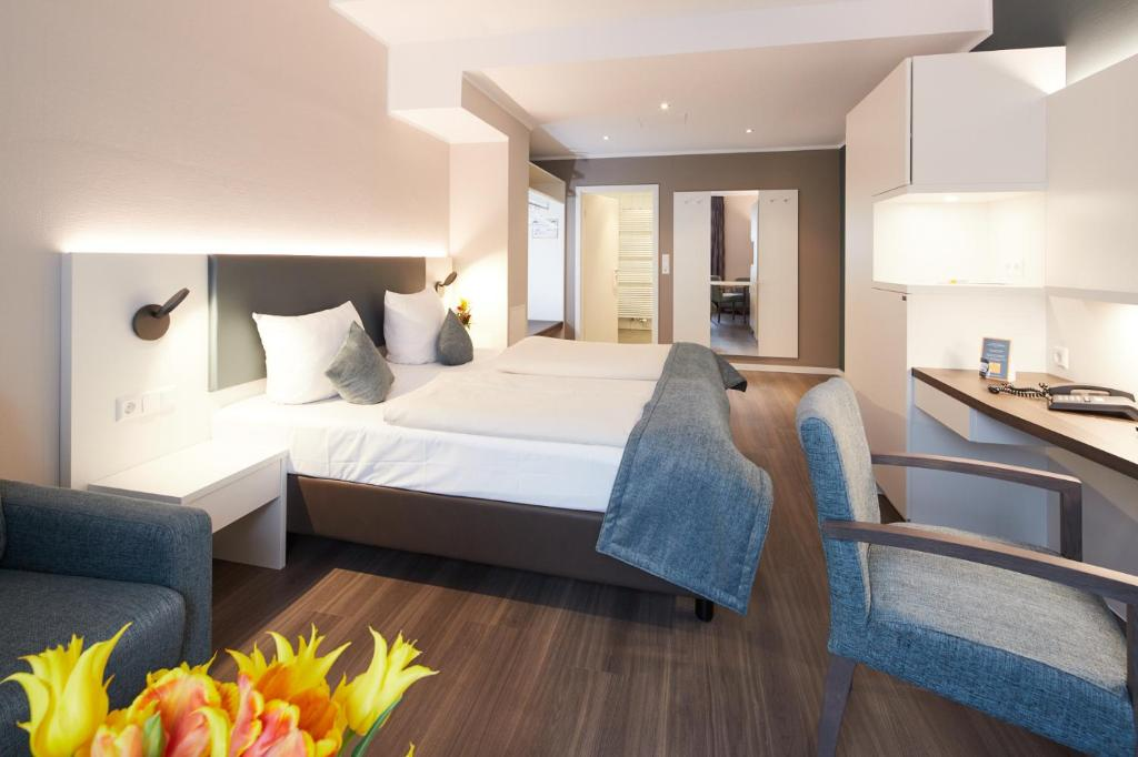 A bed or beds in a room at Stadthotel Freiburg Kolping Hotels & Resorts