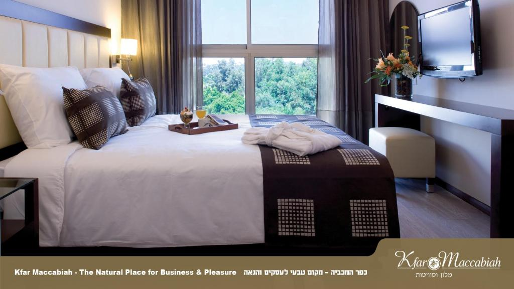A bed or beds in a room at Kfar Maccabiah Hotel & Suites