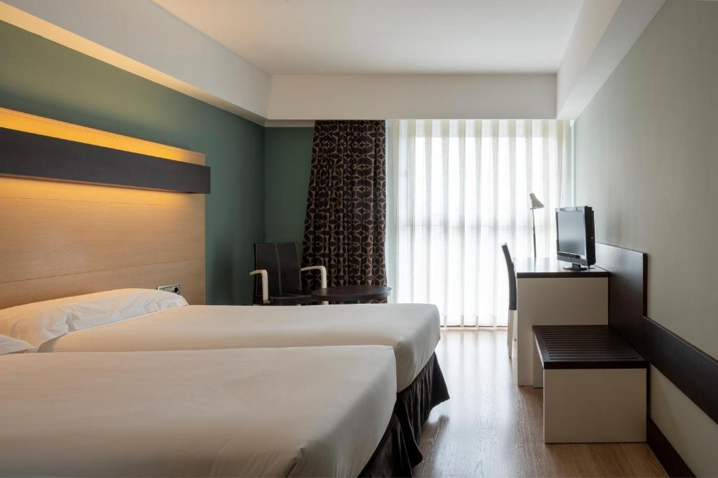 En eller flere senge i et værelse på Hotel Ciudad de Logroño