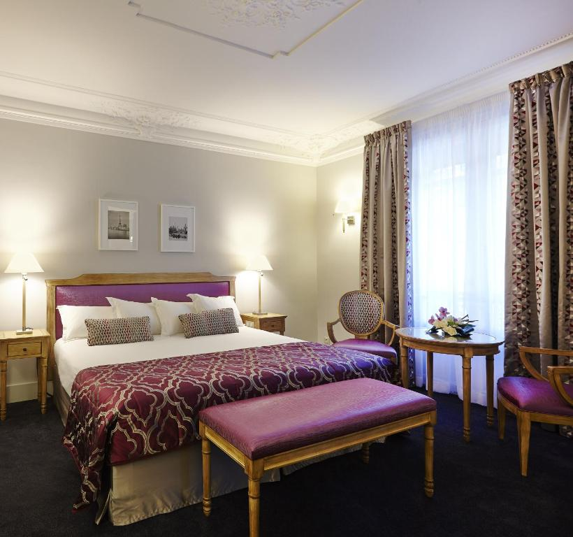 A bed or beds in a room at Royal Hotel Paris Champs Elysées