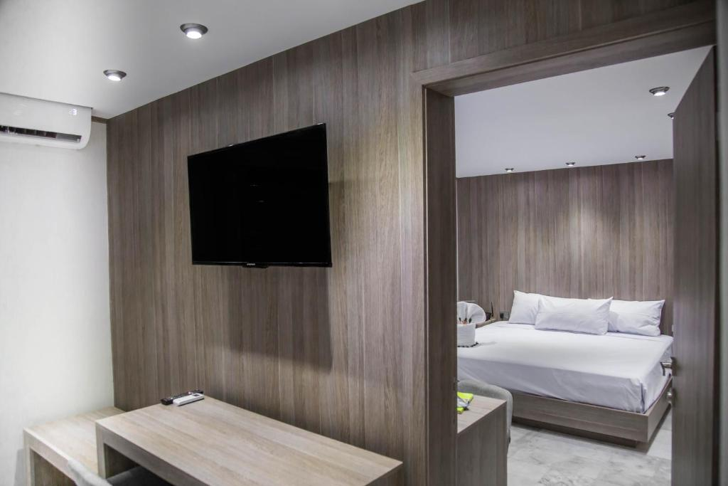 A television and/or entertainment center at Excel Sense Playacar Boutique Hotel