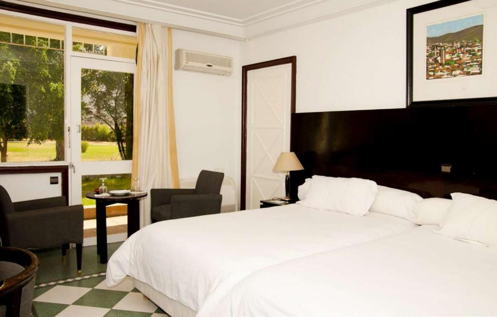 A bed or beds in a room at Hotel Ouzoud Beni Mellal