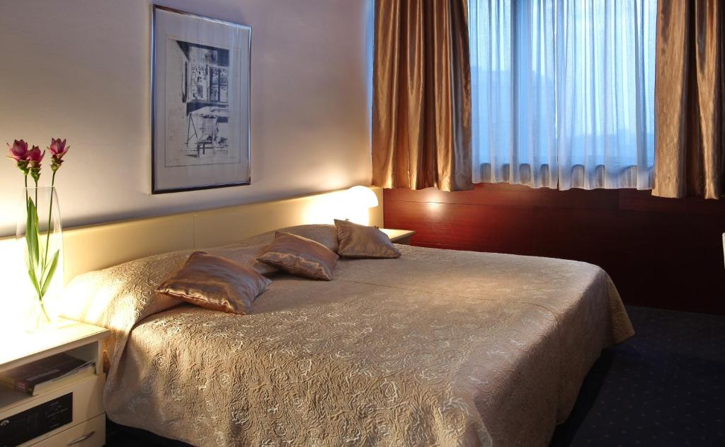 A bed or beds in a room at Hotel Slavija Garni