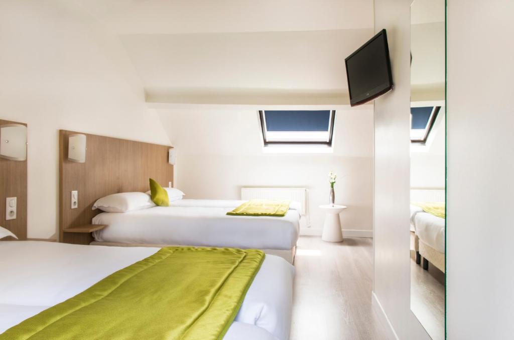 A bed or beds in a room at Bel Oranger Gare de Lyon
