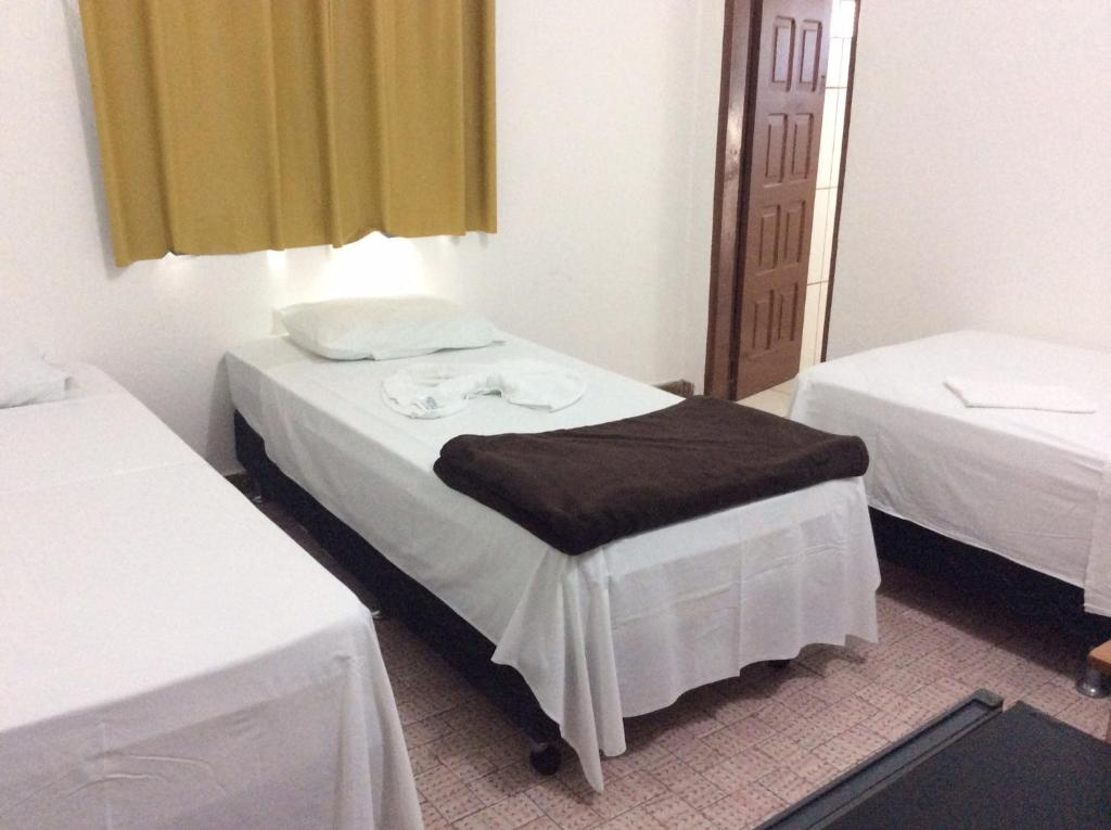 A bed or beds in a room at Hotel Pérola