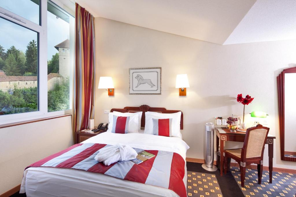 A bed or beds in a room at Hôtel aux Remparts