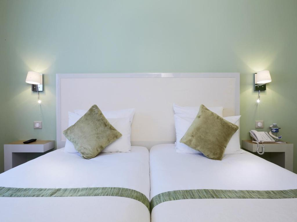 A bed or beds in a room at Kyriad Paris 18 - Porte de Clignancourt - Montmartre