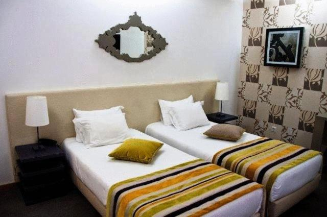 A bed or beds in a room at Paredes Design Hotel