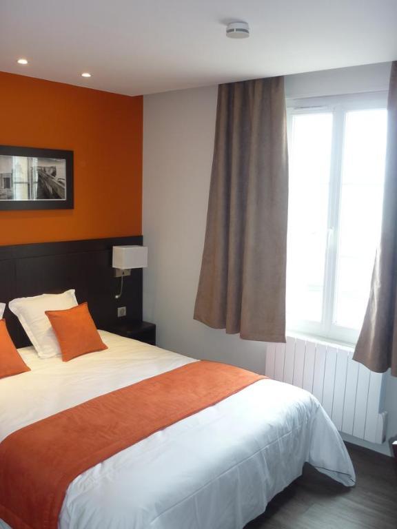 A bed or beds in a room at Hotel De La Plage