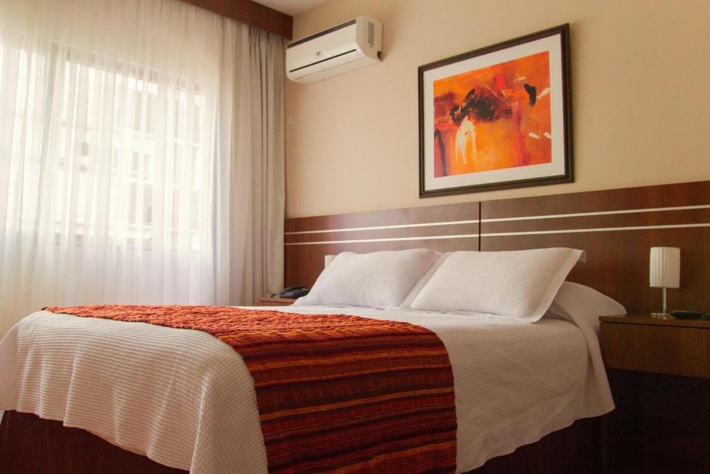 En eller flere senger på et rom på Hotel America