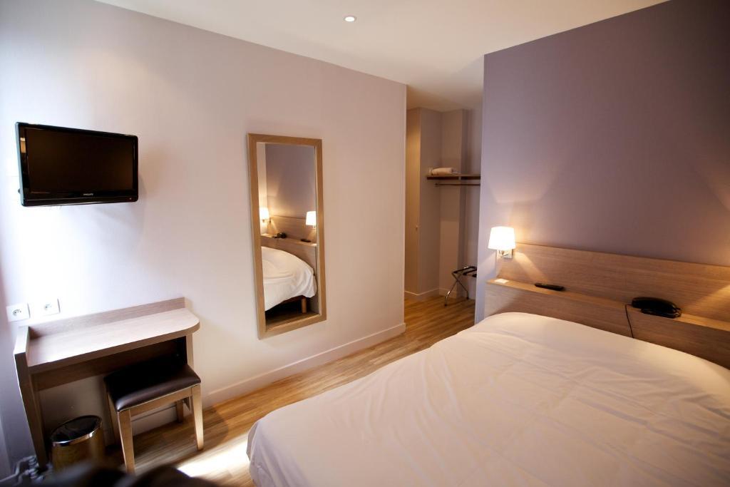 Un ou plusieurs lits dans un hébergement de l'établissement Hôtel Montchapet Dijon Centre