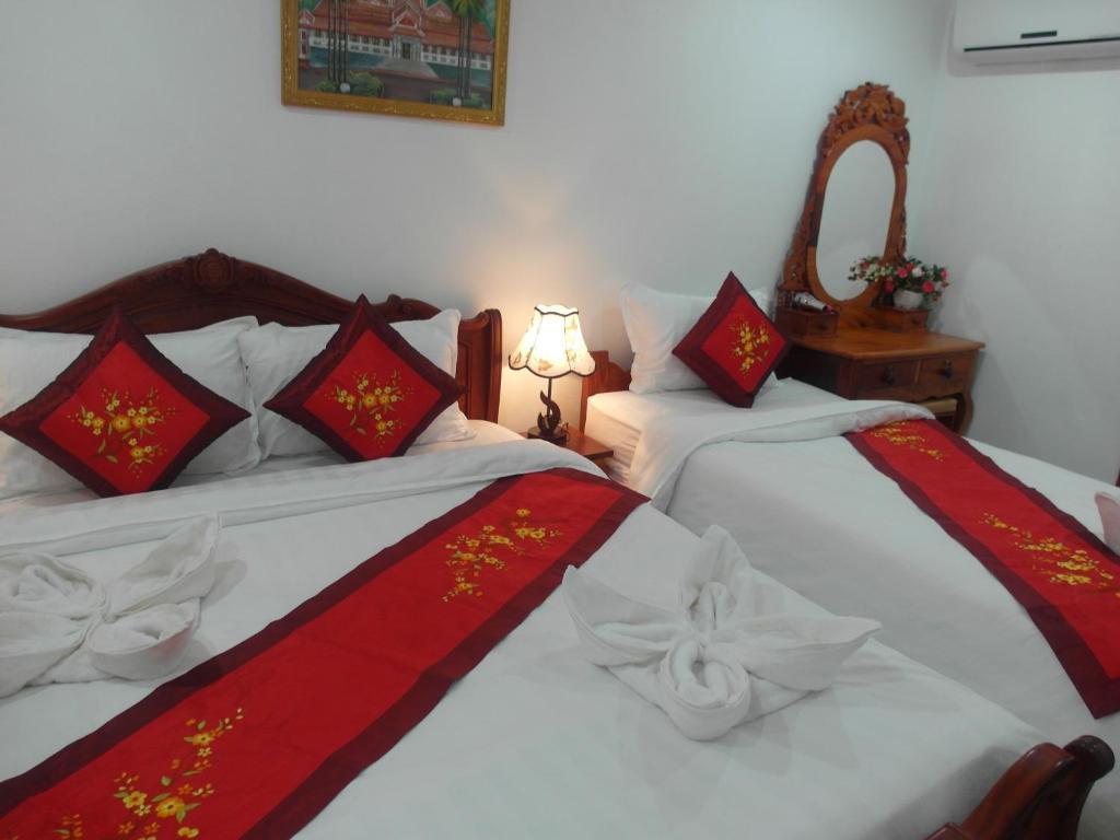 A bed or beds in a room at Nocknoy Lanexang Guesthouse