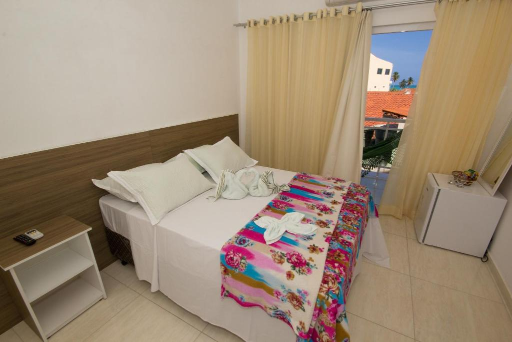 A bed or beds in a room at Pousada Verdes Mares