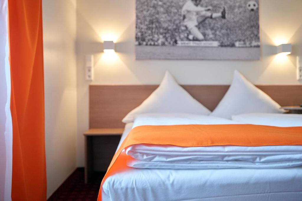 A bed or beds in a room at McDreams Hotel Mönchengladbach