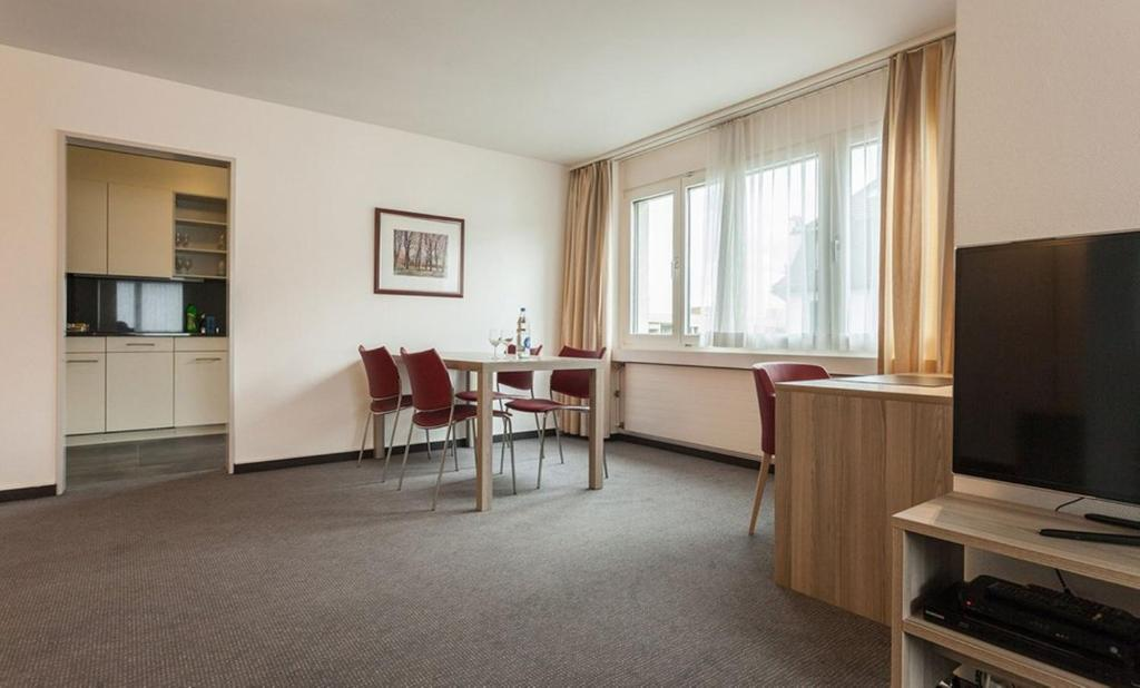 A television and/or entertainment center at EMA House Serviced Apartments Aussersihl