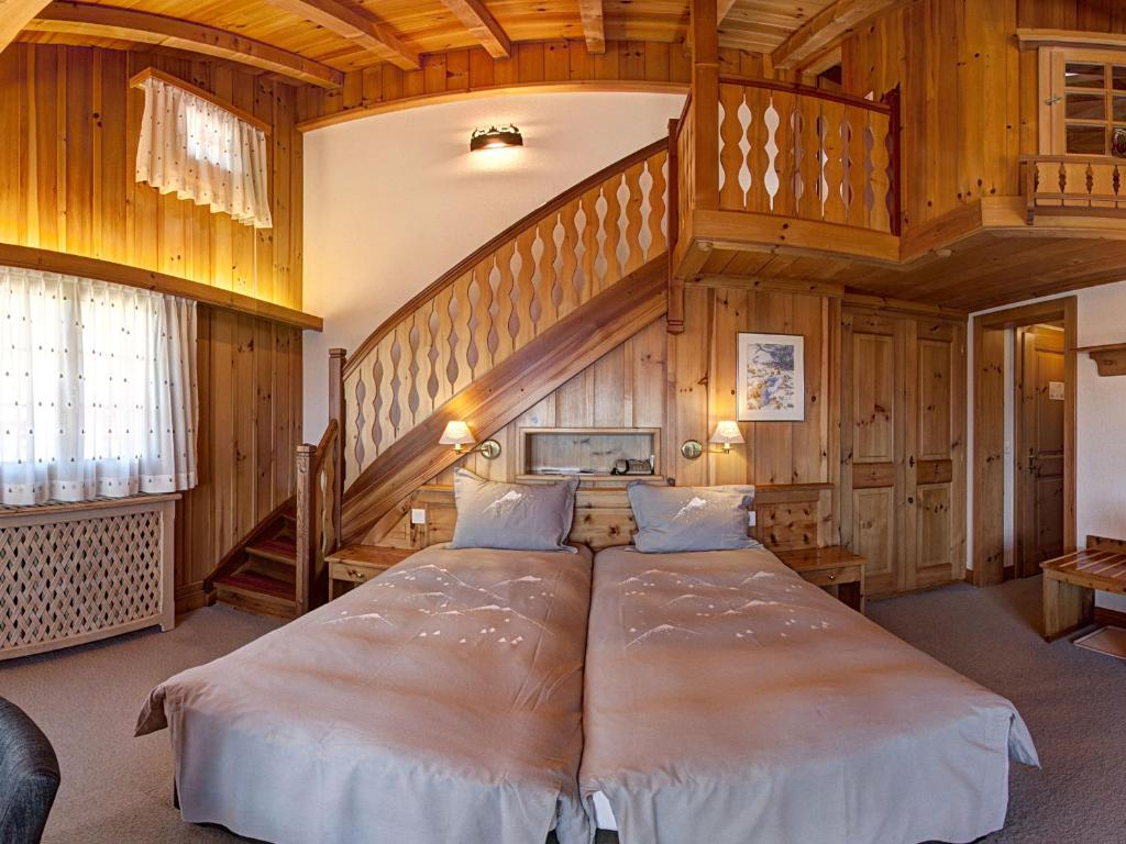 A bed or beds in a room at Alpe Fleurie Hôtel & Restaurant