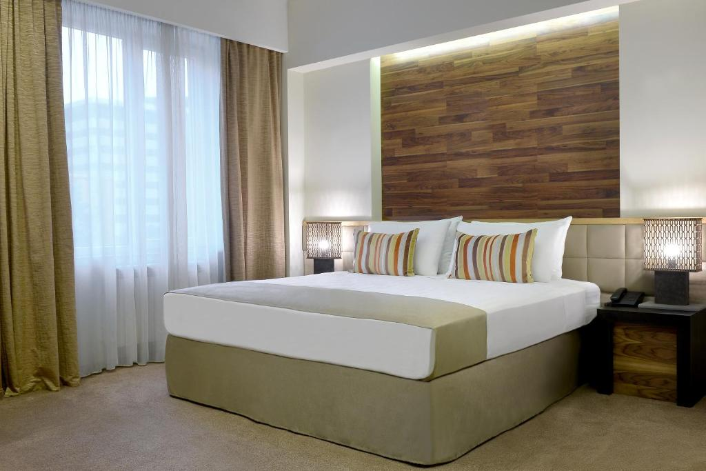 A bed or beds in a room at Minotel Barsam Suites