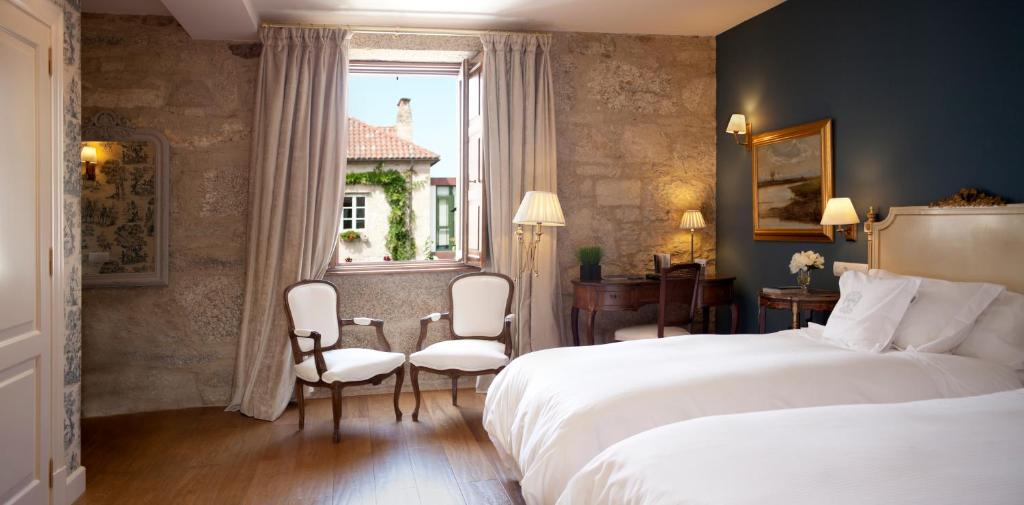 A bed or beds in a room at A Quinta Da Auga Hotel Spa Relais & Chateaux