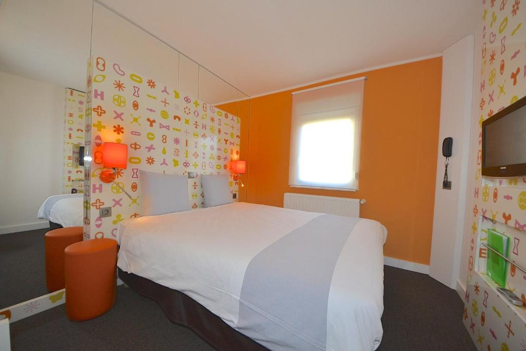 A bed or beds in a room at ibis Styles La Louvière