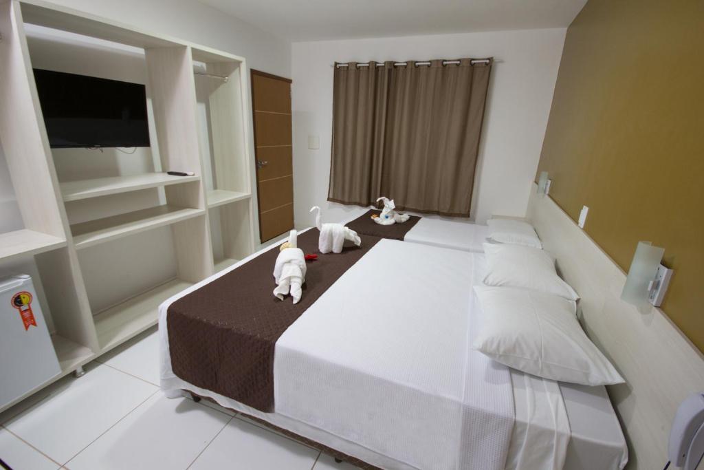 A bed or beds in a room at Pousada Maragolfinho