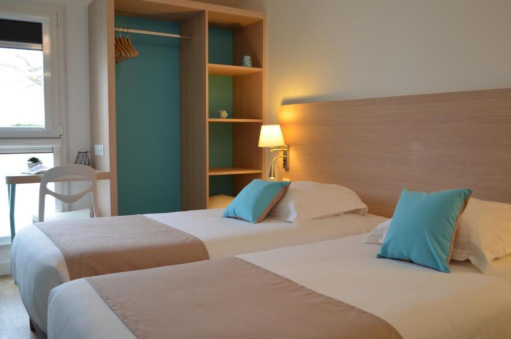 A bed or beds in a room at The Originals Boutique, Hôtel Port la Vie, Saint-Gilles-Croix-de-Vie