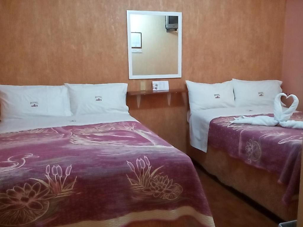 A bed or beds in a room at Hotel Aries Tlaxcala
